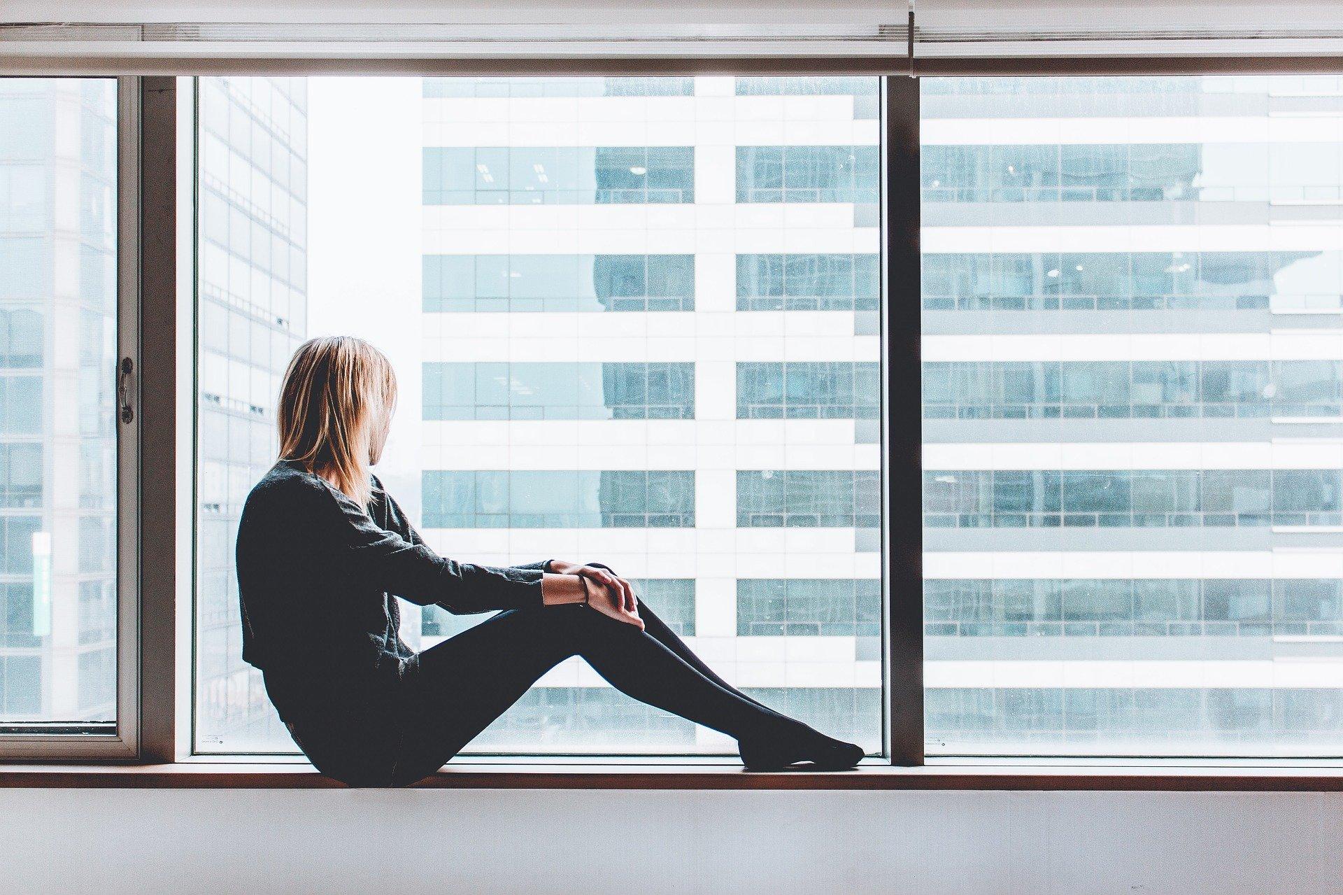 момиче гледа през прозореца
